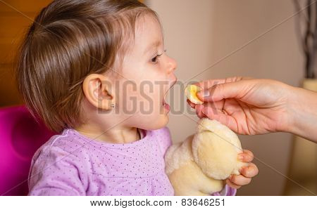 Baby eating banana slice from the hand of mother