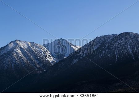 Mountain Peaks With Snow And Pine Trees