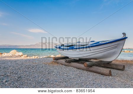 White fishing boat on sand with blue sky and water