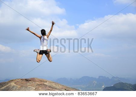 Stock Photo: freedom young asian woman jumping on mountain peak rock