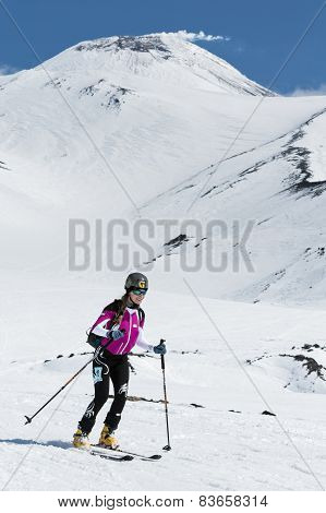 Ski mountaineering: woman ski mountaineer rides skiing from volcano