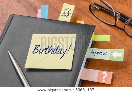 A planner with a sticky note - Birthday