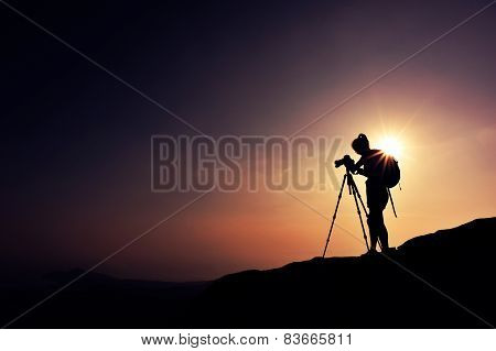 woman photographer taking photo on sunset mountain peak