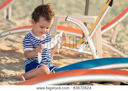 Toddler Dressed As A Sailor Playing With His Clothes Near Sunbeds On A Beach. Photo With Untradition