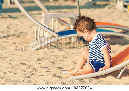 Toddler Dressed As A Sailor Sitting On A Tilted Sunbed And Exploring The Sand On A Beach. Photo With