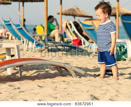 Toddler Dressed As A Sailor Standing On A Beach And Crying With Other People In Defocussed Backgroun