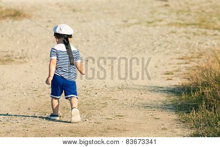 Toddler Dressed As A Sailor Walking With Determination On A Gravel Road. Photo With Untraditional Co