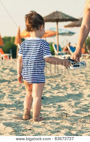 Woman Hand Giving Flip Flops To A Toddler With Sailor Shirt On A Beach. Photo With Untraditional Col