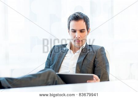 Serious Young Businessman Reading His Tablet PC