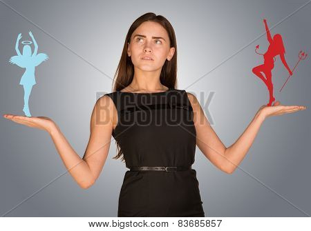 Woman making choice between angelic and devilish figures