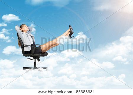 Businesswoman dreaming in clouds