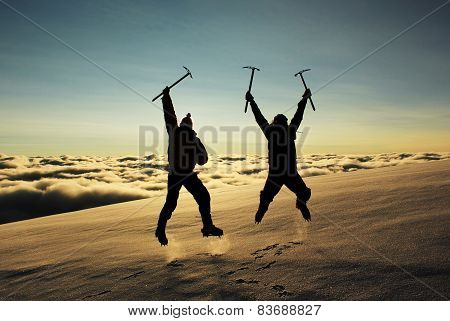 jumping people on a snowy slope in the mountains against sun