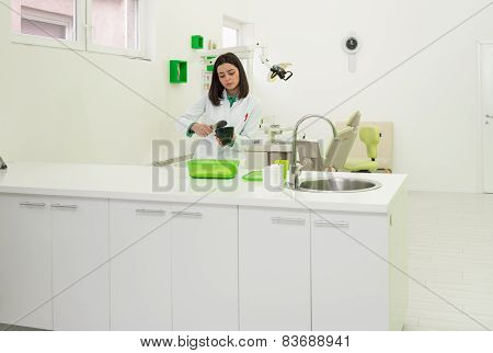 Young Female Dentist Working On The Mould