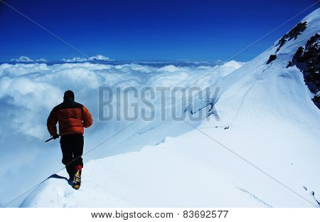 man goes on a snowy slope in the mountains with ice axe