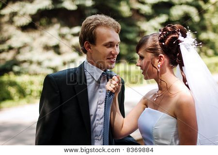 Beautiful Couple Newlywed, Bride Pulling Her Groom In By His Necktie.