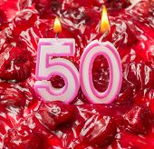 foto of 50th  - Cherry cheese cake with burning candles for 50th birthday