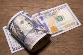stock photo of one hundred dollar bill  - Roll of One Hundred Dollar Bills on wood table background  - JPG