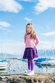 pic of pullovers  - Outdoor portrait of a cute little girl in a port on a nice day, wearing pink pullover and purple skirt and tights