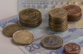 stock photo of copper coins  - Euro coins stacked on 20 Euro bills and a 5 Euro bill - JPG