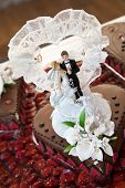 foto of figurines  - Close up Wedding Chocolate Cake with Couple Figurines in a White Laced Heart
