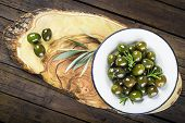 stock photo of kalamata olives  - Green olives with rosemary and olive oil on a vintage plate on the table of the kitchen - JPG