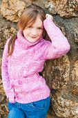 stock photo of pullovers  - Outdoor portrait of adorable little girl wearing pink pullover - JPG