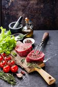 pic of meats  - Raw fresh marbled meat Steak seasoning and meat fork on dark marble background - JPG