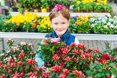 picture of flower shop  - Adorable little girl choosing flowers in flower shop on early spring - JPG