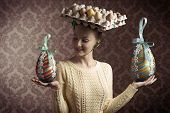 foto of old-fashioned  - funny easter shoot of brunette female with yellow dress and bizarre hat with eggs in carton box  - JPG