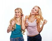 image of flutter  - Beautiful girls sisters headphones listening to music with fluttering hair - JPG