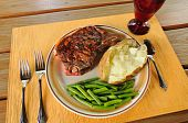 picture of baked potato  - A dinner of grilled strip steak baked potato and green beans set on a picnic table - JPG