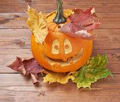 stock photo of jack-o-lantern  - Jack o lantern smiling happy pumpkin composition over the maple leaves and wooden surface - JPG