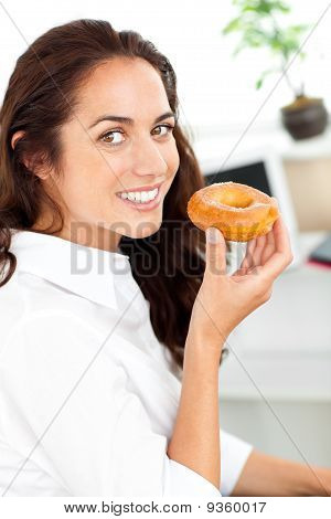 Smiling Hispanic Businesswoman Holding A Doughnut