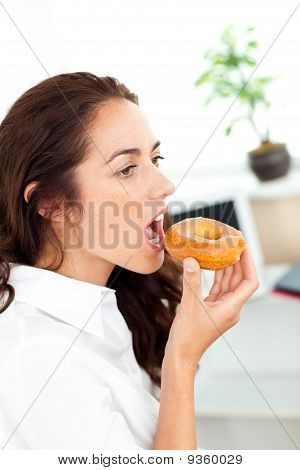 Charming Hispanic Businesswoman Eating A Doughnut