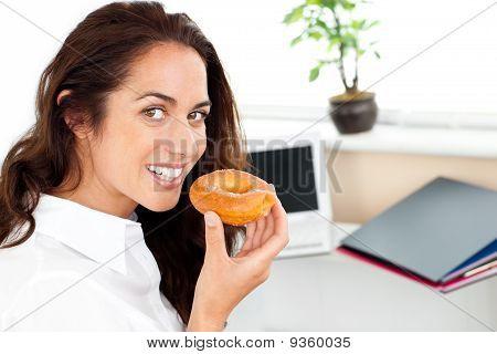 Happy Hispanic Businesswoman Eating A Doughnut