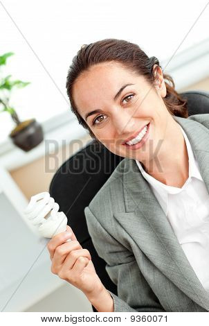 Bright Hispanic Businesswoman Holding A Light Bulb Sitting At Her Desk