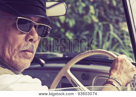 Older man with glasses driving a car