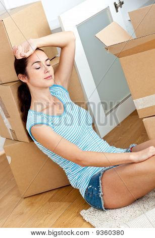 Tired Hispanic Woman Lying On The Floor With Cardboards