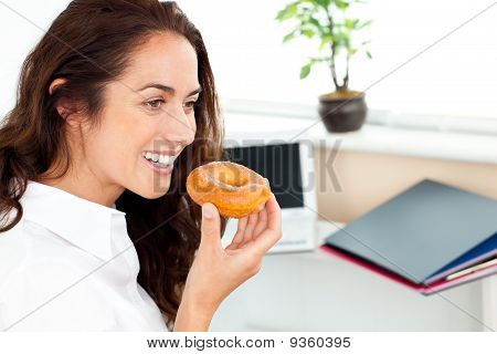 Hispanic Businesswoman Eating A Doughnut In Her Office