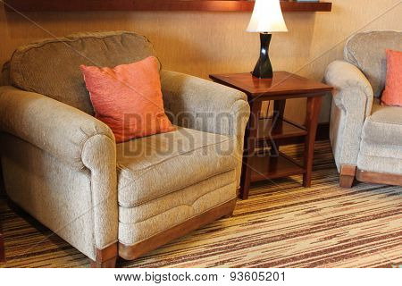 A comfy armchair with orange pillow near a small table