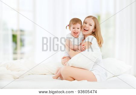 Happy Family Mother And Baby Daughter Playing And Laughing Baby Kissing In Bed