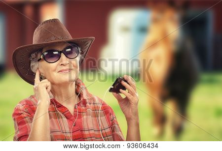 Old cowgirl using music apps for smartphone