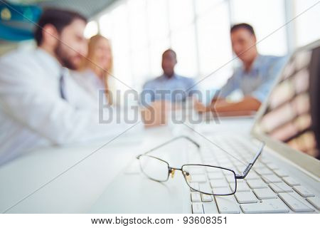 Eyeglasses on laptop keypad with group of partners on background