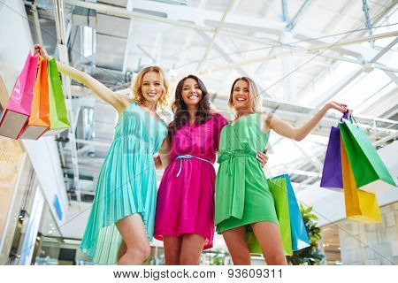 Happy shopaholics with paperbags looking at camera