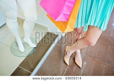 Legs of a shopper and those of mannequin in the mall