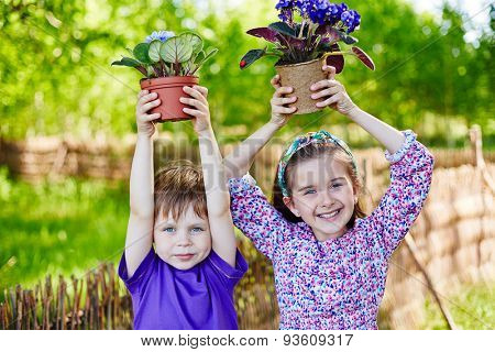 Happy kids with newly planted violets looking at camera in natural environment