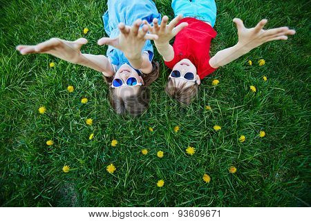 Carefree children in sunglasses lying on green lawn with yellow dandelions