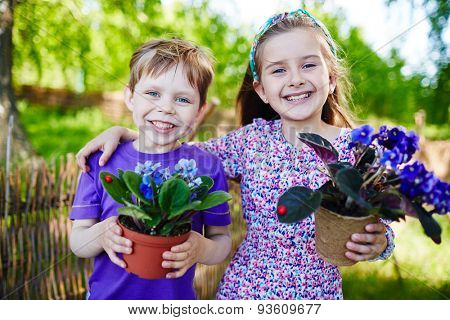 Friendly boy and girl with garden violets looking at camera in natural environment