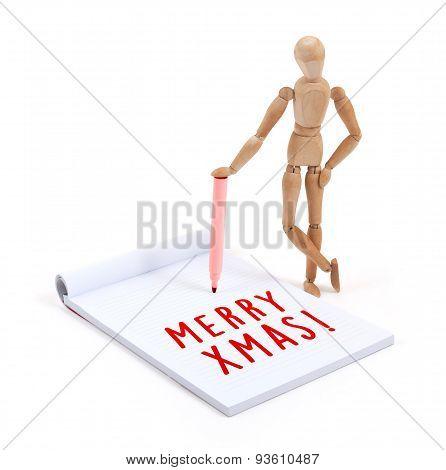 Wooden Mannequin Writing In Scrapbook - Merry Xmas