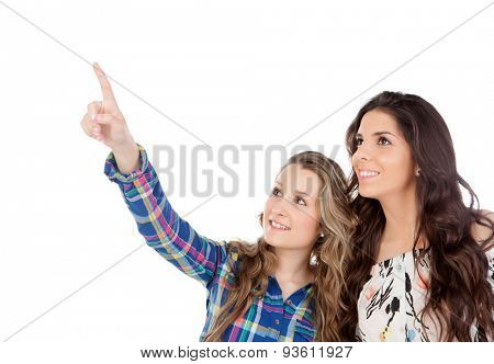 The best friends. Two pretty women indicating something with the finger isolated on a white background